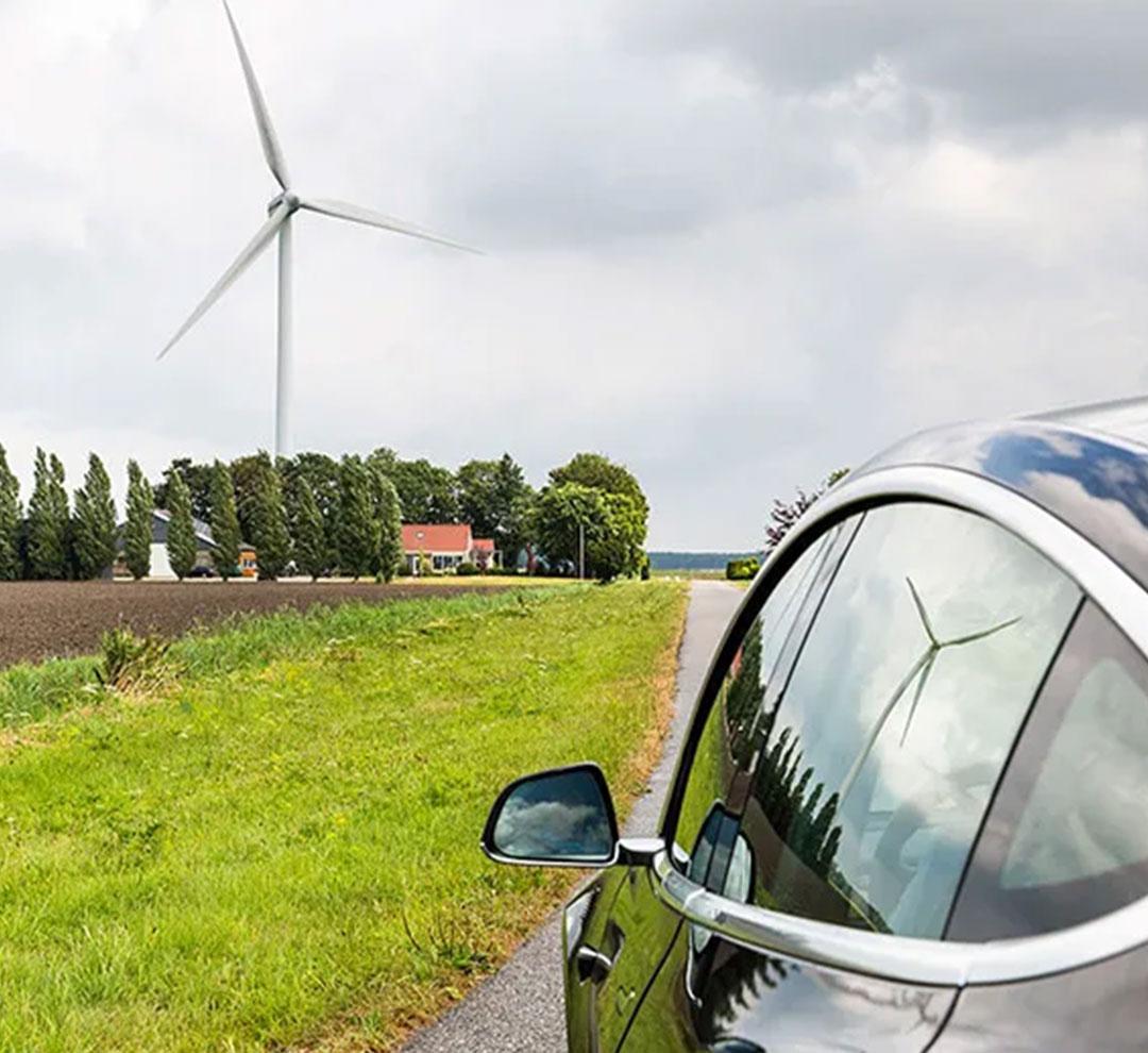 Ein elektrisches Auto auf der Straße mit einer Windmühle daneben